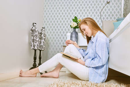 Beautiful girl having a rest in her cozy bright bedroom, she is sitting next to the bed and reading a book. Home interior, furniture. Lifestyle.
