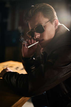 Handsome young man in a leather jacket and sunglasses sits at the bar and smokes a cigarette. Lifestyle.