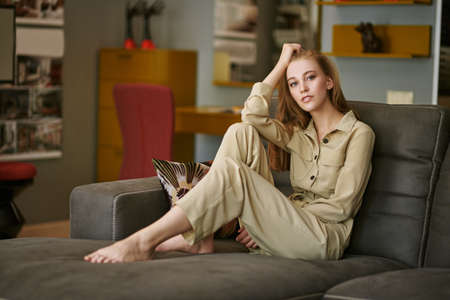 Happy life, happy people concept. Portrait of a beautiful blonde girl having a rest on a sofa in her cozy living room. 免版税图像