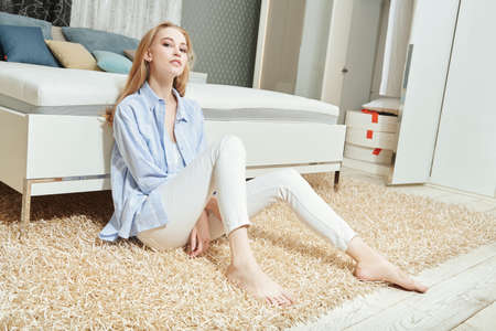 Lifestyle. Beautiful girl having a rest in her cozy bright bedroom, she is sitting on a soft carpet next to the bed. Home interior, furniture. 免版税图像