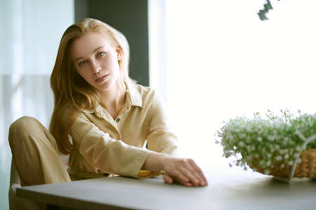 Portrait of a beautiful blonde girl sitting relaxed at a table in her living room. Happy people and lifestyle concept. 免版税图像