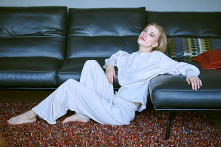 Beautiful happy girl having a rest in her cozy living room, she is sitting on a floor by a leather sofa. Home interior, furniture. Lifestyle.