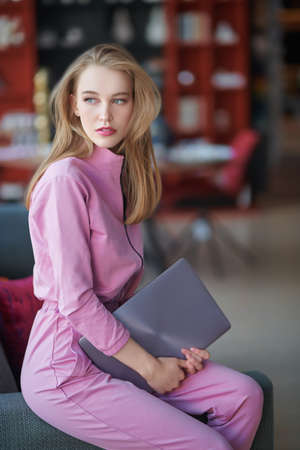 Confident young woman sits on a sofa with her laptop at home. Business concept. 免版税图像