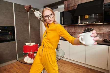 Attractive young woman in bright yellow overalls is making coffee at home in the kitchen. Modern interior, furniture for the kitchen. Home cooking. 免版税图像