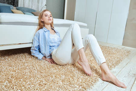 Beautiful girl having a rest in her cozy bright bedroom, she is sitting on a soft carpet next to the bed. Home interior, furniture. Lifestyle.