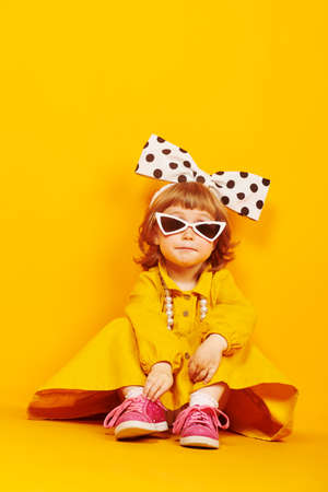 Kid's fashion. Lovely little child girl in fashionable dress, big bow and sunglasses poses on a bright yellow background. Pin-up style. Copy space.