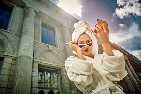 Glamorous lifestyle. Stunning woman in a white bathrobe with a white towel on her head paints her lips with red lipstick, standing on the street of a big city.