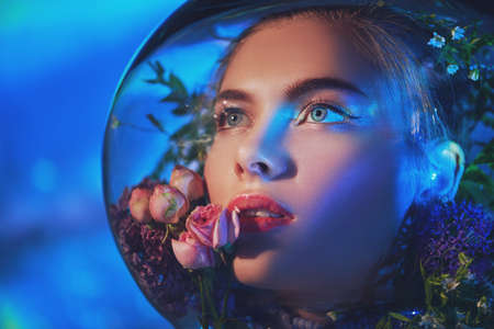 Beautiful girl in a spacesuit filled with flowers looks up with hope on the background of outer space. Air pollution, environmental disaster.