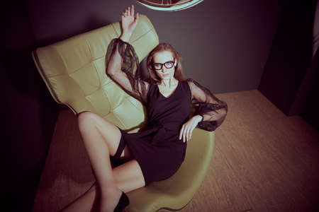 Fashionable lady in black evening dress and stylish glasses poses on a leather armchair in a luxury apartment. Fashion shot.