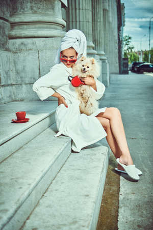 Extravagant lady in a white terry dressing gown with a white towel on her head and elegant sunglasses alluring on a city street with a cup of tea and her small fluffy dog. Beauty, fashion.