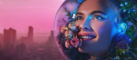 Ecological disaster. Beautiful girl in a spacesuit filled with flowers looks up with hope and smiles against the backdrop of a large industrial city. Copy space. 免版税图像