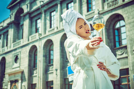 Stunning woman in a white bathrobe with a white towel on her head alluring on a city street with a glass of champagne and a cigarette. Glamorous lifestyle. Fashion shot. 免版税图像
