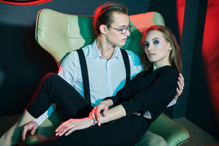 Handsome young man hugs his beloved woman, sitting on an armchair in a luxury apartment, dating. Glamorous lifestyle. Fashion shot.