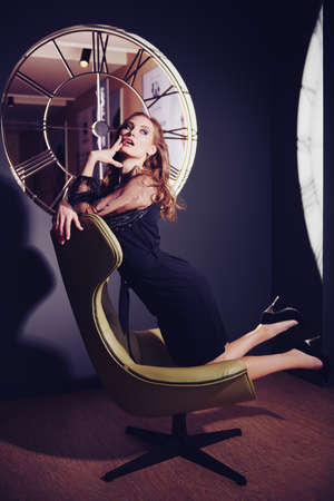 Portrait of a stunning fashionable woman in a black evening dress posing on a luxurious leather armchair. Modern interior, furniture. Fashion shot. 免版税图像