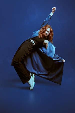 Professional modern style dancer dancing at studio on a dark blue background 免版税图像