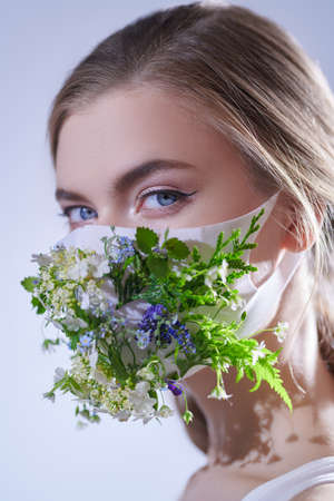 Fashion, beauty and healthcare. Portrait of a beautiful blonde girl posing in a mask decorated with green plants and flowers. Studio portrait. 免版税图像