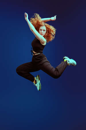 Professional modern style dancer jumping at studio on a dark blue background