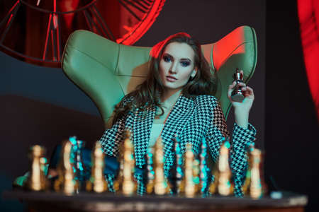 Elegant business lady in stylish suit plays chess in a modern luxury interior. Fashion shot. Business style. 免版税图像