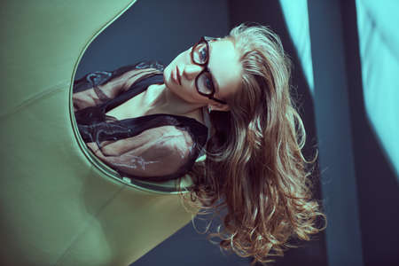 Modern glasses style. Portrait of a beautiful young woman posing in black evening dress and elegant glasses in a luxury leather armchair. Beauty, fashion. 免版税图像