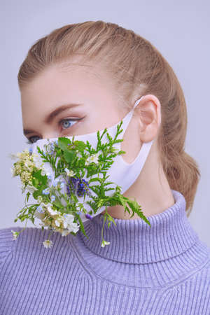 Portrait of a beautiful blonde girl posing in a mask decorated with green plants and flowers. Fashion, beauty and healthcare. Studio portrait.