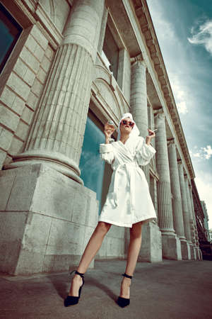 Luxurious lifestyle. Elegant girl in a white terry dressing gown with a white towel on her head and high heels alluring on a city street with a glass of champagne and cigarette. Fashion shot.