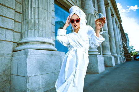 Attractive girl in a white bathrobe and with a white towel on her head walks along a city street with a glass of wine and cigarette. Glamorous lifestyle. Fashion shot. 免版税图像