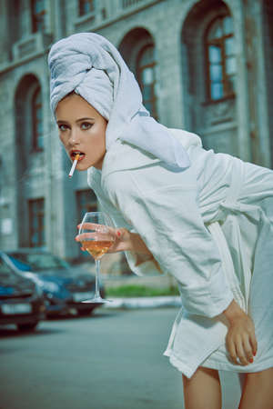 Glamorous lifestyle. Stunning woman in a white bathrobe with a white towel on her head alluring on a city street with a glass of champagne and a cigarette. Fashion shot.