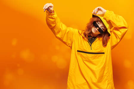Portrait of a stylish girl in yellow hoodie and sunglasses poses at studio on a yellow background. Youth style. Modern hip-hop dancer.