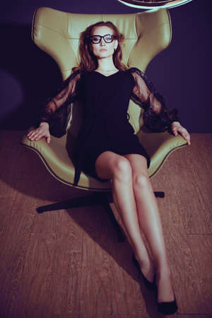 Fashion shot. Full length portrait of a fashionable lady in black evening dress and stylish glasses sitting in a leather armchair in a luxury apartment. 免版税图像