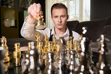 Strategic decision in business. Well-groomed smart man in elegant clothes plays chess in a modern luxury interior. 免版税图像