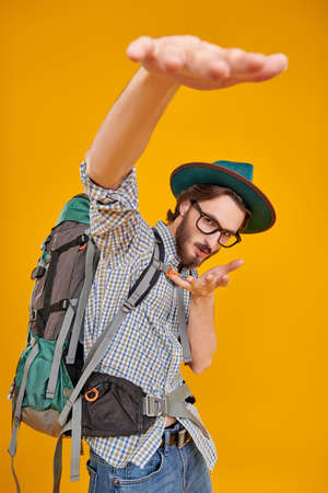 Tourism and travel, adventure. Portrait of an emotional funny tourist man with backpack on a yellow background.