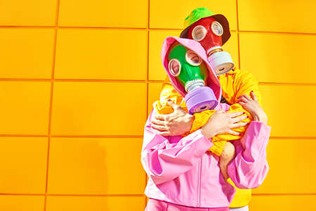 Love and the apocalypse. Two tender lovers in bright clothes and gas masks stand hugging each other by a yellow industrial wall. Environmental disaster.