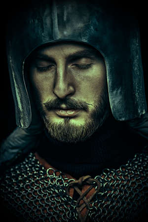 Close-up portrait of a brave medieval knight in armor closed his eyes in prayer.