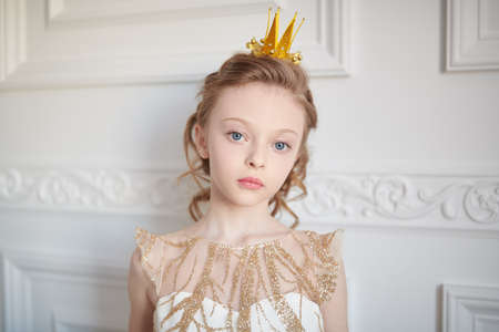 Fairy tales. Beautiful little girl princess in festive dress and a crown stands in white classic apartment. Childhood dreams.