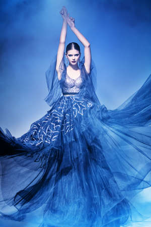 Fashion and beauty. Gorgeous fashion model girl poses in motion in a luxury evening dress. Full length studio portrait.
