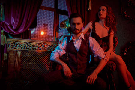 Glamorous couple in love. Beautiful lady in sexual black lingerie and a handsome man in elegant suit in a luxury vintage apartment. Fashion shot.
