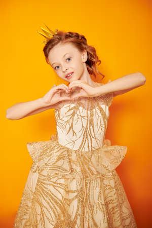 Portrait of a charming little princess girl in a golden dress and a crown showing a heart and smiling at camera. Dreams and kid's fashion. Yellow background.