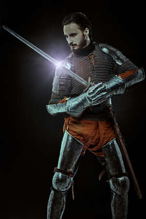 Portrait of a medieval knight with a sword and armor in fighting pose on a black background. 写真素材