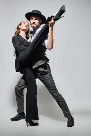 Beautiful couple of young people in love dancing passionate tango. Sexual girl and handsome man in love. Fashion and love. Full length portrait on a gray background.