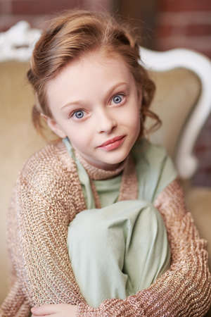 Cute eight year old girl with big blue eyes looking at the camera.