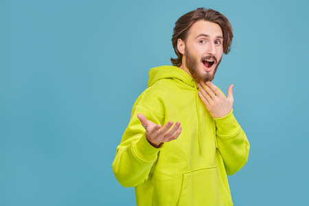 Young emotional man laughing and pointing to the camera. People, emotions. Studio portrait on a blue background with copy space.