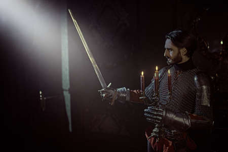 A medieval knight in armor standing with candles and his sword in the castle.