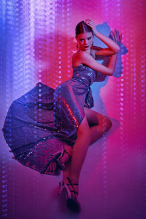 High fashion shot. Beautiful dancer girl poses in a long shiny evening dress and high heels in mixed neon light. Ballet show. 写真素材