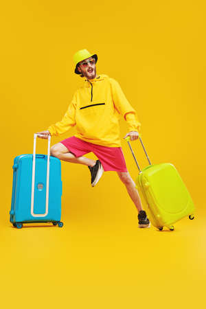 Cool young man in bright trendy clothes goes on vacation with suitcases. Vacation and travel. Studio portrait on a yellow background.