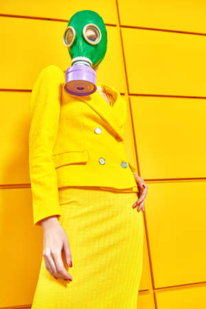 Fashion of the future. Full length portrait of a woman in elegant yellow suit and green gas mask posing by a yellow industrial wall. Environmental disaster, apocalypse. 免版税图像