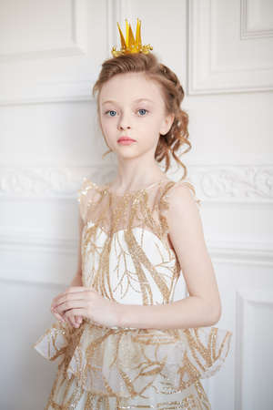 Beautiful little girl princess in festive dress and a crown stands in white classic apartment. Childhood dreams. Fairy tales.