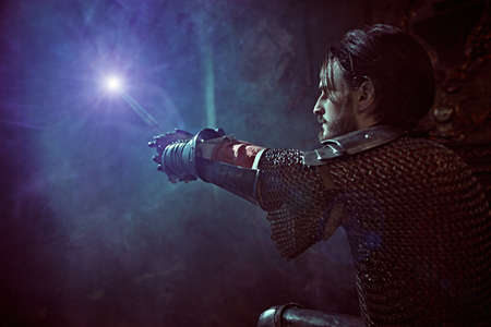 The noble knight in armor knelt down and raised his sword, looking at the light in the castle. Romance. 写真素材
