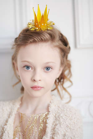 Portrait of a beautiful little princess girl in a golden dress and a crown. Kid's fashion. 免版税图像