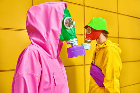 Two fashion models in bright clothes and gas masks stand by a yellow industrial wall. Modern art concept. Global ecological disaster.