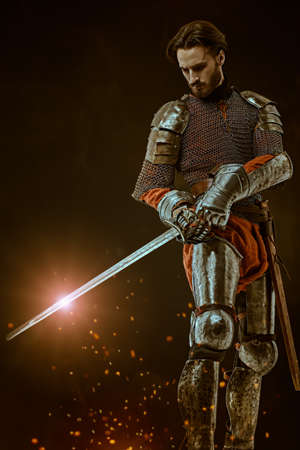 Full length portrait of a brave medieval knight with sword and armor on a dark background with sparks of fire. 写真素材
